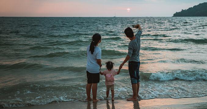 Vater, Mutter und Tochter blicken ins Meer und der Vater macht mit dem Smartphone ein Selfie der ganzen Familie.