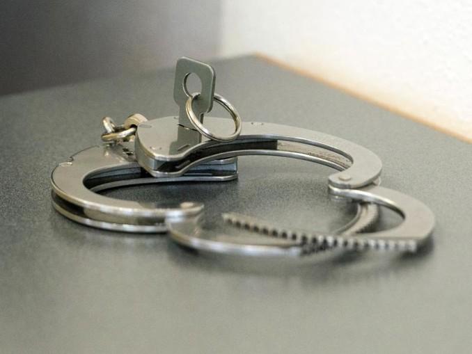 Handschellen liegen auf einem Tisch. /Archiv