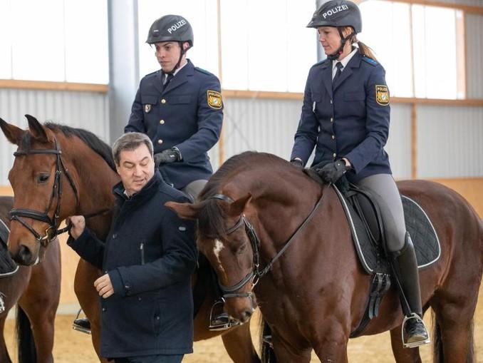 Markus Söder (CSU), Ministerpräsident von Bayern, steht neben den Polizeireitern Robin Philipp mit Pferd Hermes und Stephanie Sendker mit Pferd Noris bei der Vorstellung der neuen Reitergruppe der mittelfränkischen Polizei.