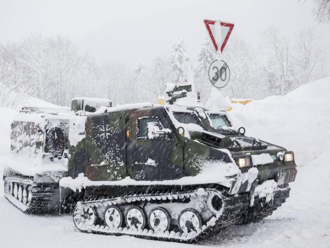 Ein Kettenfahrzeug der Bundeswehr unternimmt eine Versorgungsfahrt zur Siedlung Buchenhöhe in Berchtesgaden.