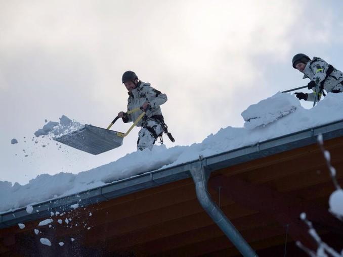 Kräfte der Bundeswehr räumen das Dach der Watzmann-Therme in Berchtesgaden vom Schnee.