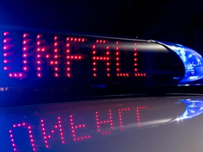Das Blaulicht auf einem Fahrzeug der Polizei und der Schriftzug «Unfall» leuchten in der Dunkelheit. /Archiv