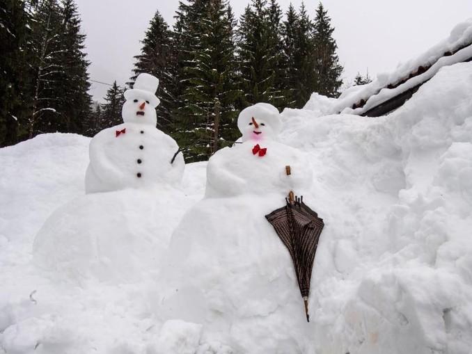 Schneemann und eine Schneefrau im Regen.