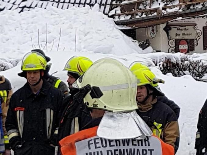 Feuerwehrleute stehen an einer Einsatzstelle im Chiemgau, an der das Dach eines Hauses teilweise eingestürzt ist.