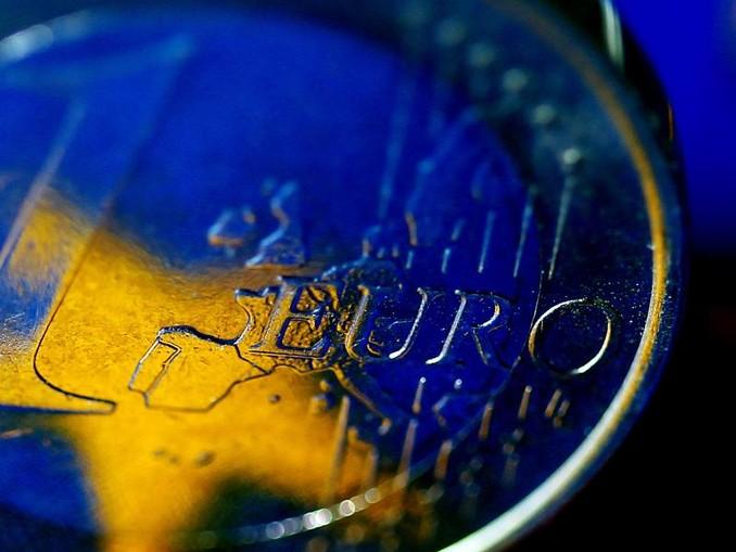 Die Fahne der Europäischen Union (EU) spiegelt sich in einer Euro-Münze. Foto:Oliver Berg/Archiv