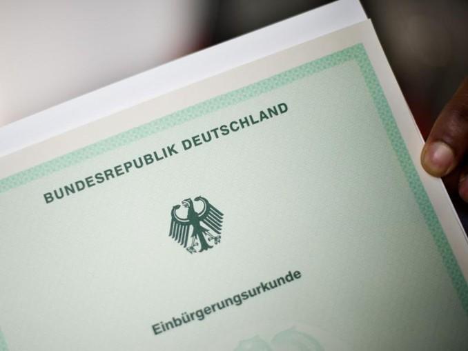 EinMann hält eine Einbürgerungsurkunde in der Hand. /Archivbild