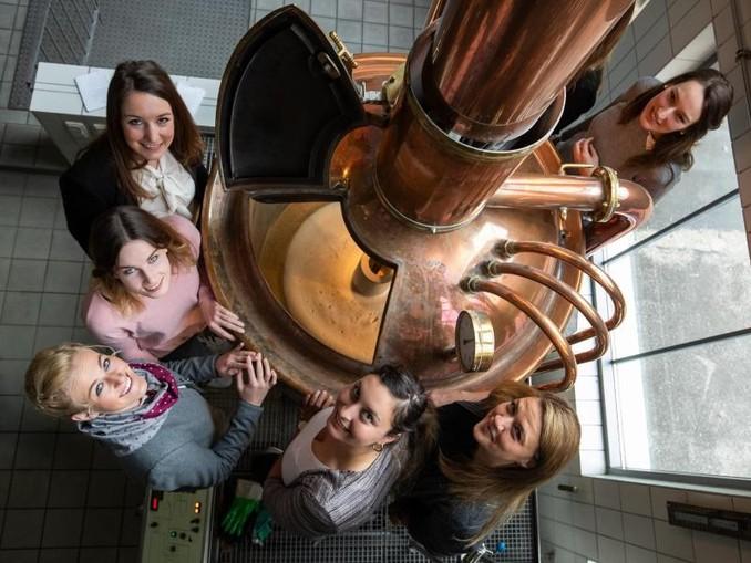 """Die Finalistinnen bei der Wahl der bayerischen Bierkönigin stehen in der """"Gläsernen Brauerei"""" an einem Kessel. Foto:Daniel Karmann/Archiv"""