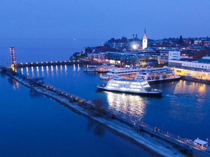 Eine Autofähre fährt zur Blauen Stunde aus dem Hafen auf dem Bodensee (Luftaufnahme). /Archivbild