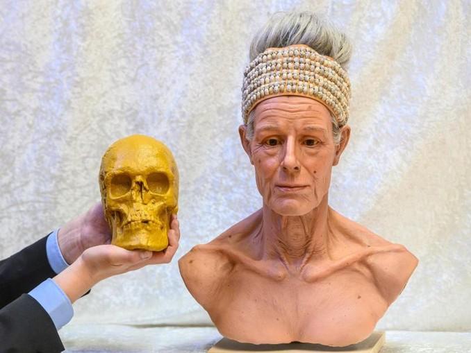 Die Nachbildung des Schädels der «Toten von Niederpöring» wird neben die Rekonstruktion des Gesichtes gehalten. Foto:Armin Weigel