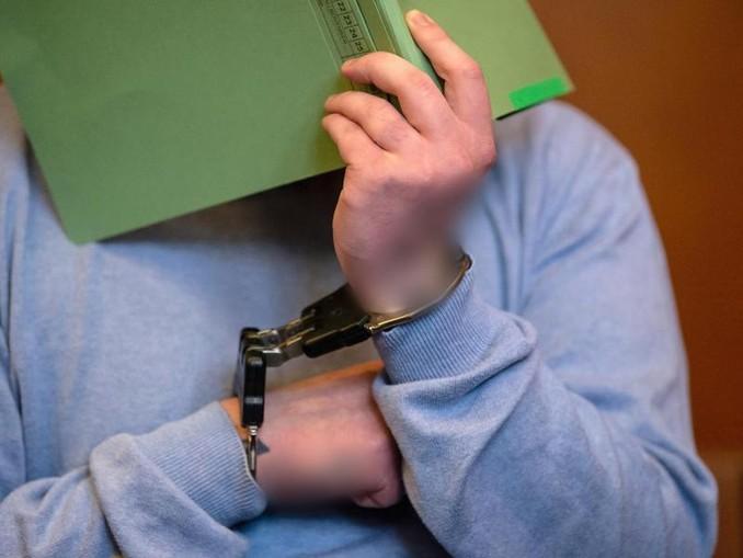 Der Angeklagte sitzt mit einem Aktendeckel vor dem Gesicht auf der Anklagebank im Gerichtssaal. Foto:Swen Pförtner