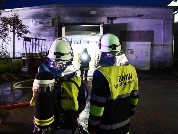Einsatzkräfte der BMW-Werksfeuerwehr stehen vor einer Halle auf dem Werksgelände. Foto:Tobias Hase