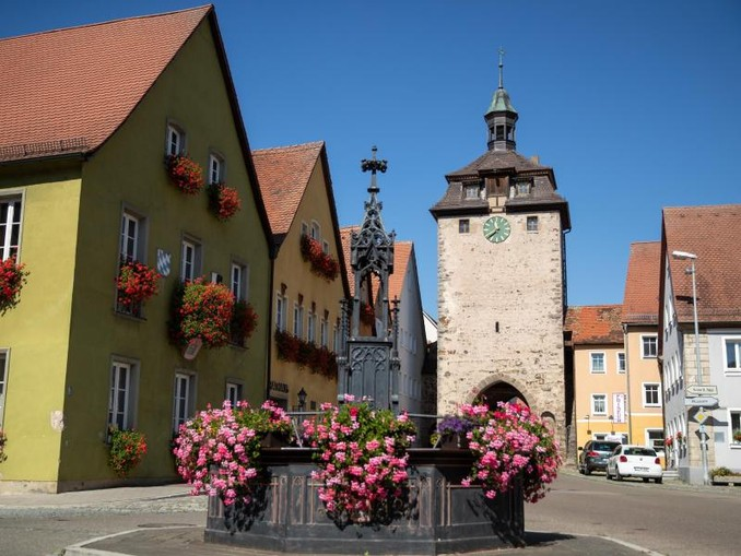 Der historische Röhrenbrunnen steht vor dem Rathaus und dem Oberen Tor Turm in Leutershausen.