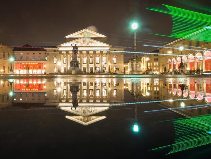 Die bayerische Staatsoper spiegelt sich in einer Pfütze auf der Residenzstraße. Foto:Peter Kneffel/Archiv