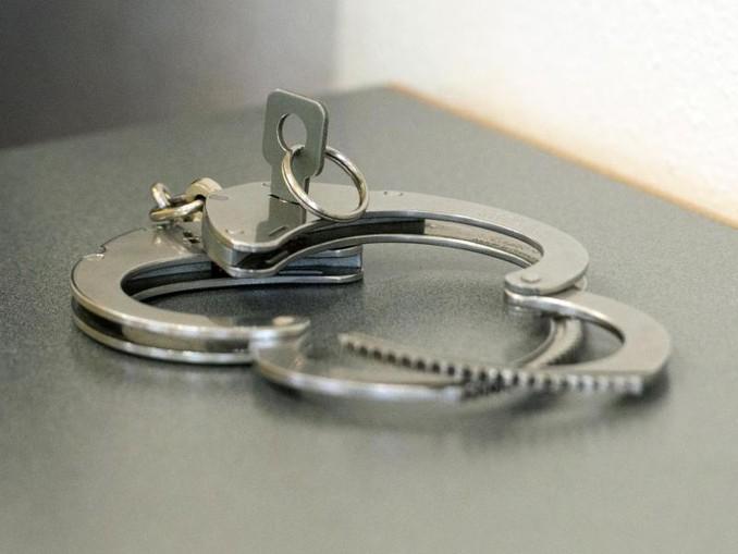 Handschellen liegen auf einem Tisch. /Archivbild