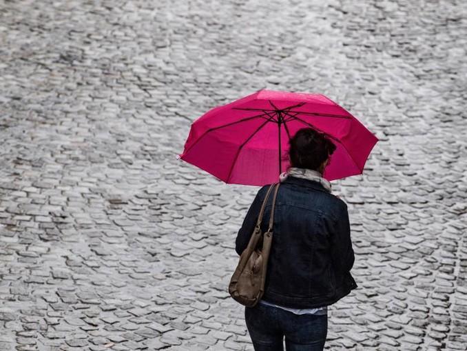 Ein Frau geht mit Regenschirm über eine Straße. Foto:Hendrik Schmidt/Archiv