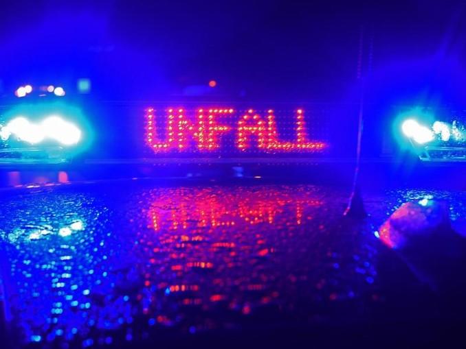 Blaulicht und der Schriftzug Unfall spiegeln sich auf einem Polizeiwagen. /dpa/Archivbild