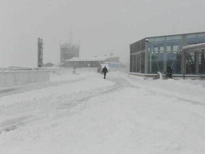 Ein Mann geht über die verschneite Dachterasse von der Zugspitze. /dpa/Archivbild