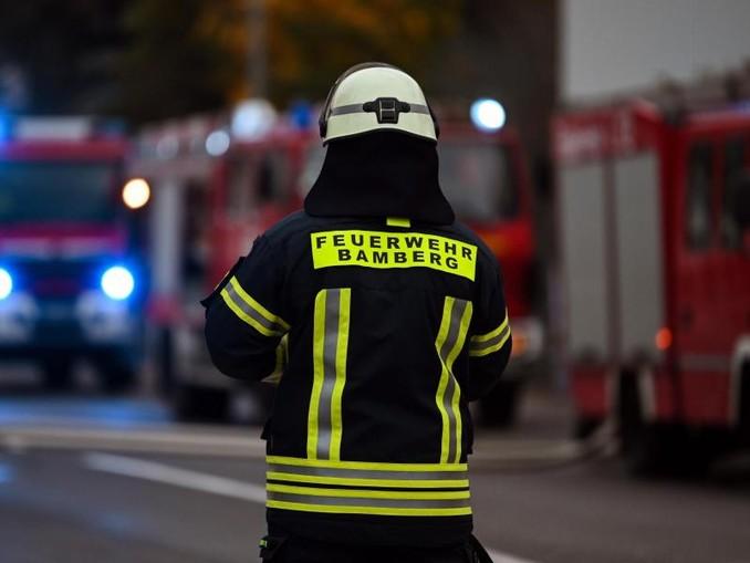 Ein Feuerwehrmann steht bei Nachlöscharbeiten vor mehreren Feuerwehreinsatzfahrzeugen. /dpa/Archivbild