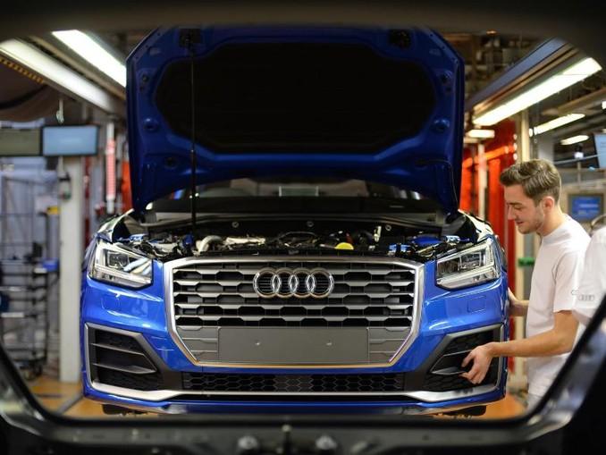 Ein Mitarbeiter bringt an einem Fließband im Audi-Werk das Frontende an einem Audi an. Foto: dpa