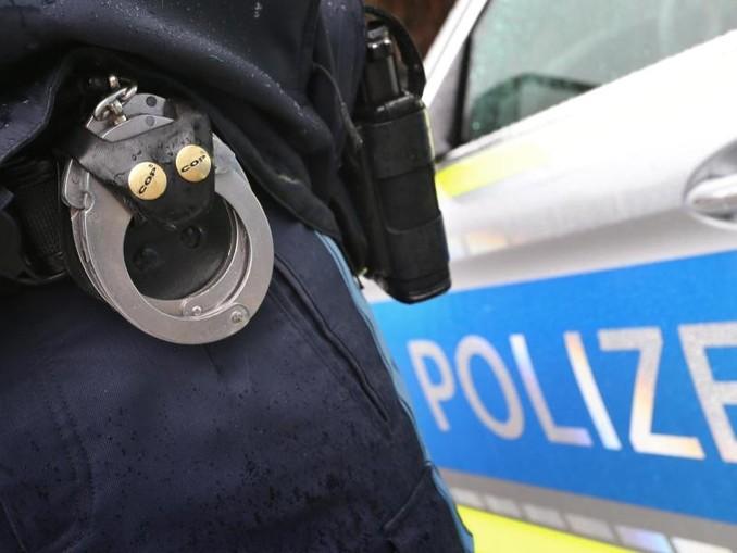 Ein Polizist mit Handschellen und einer Pistole. /dpa/Archivbild