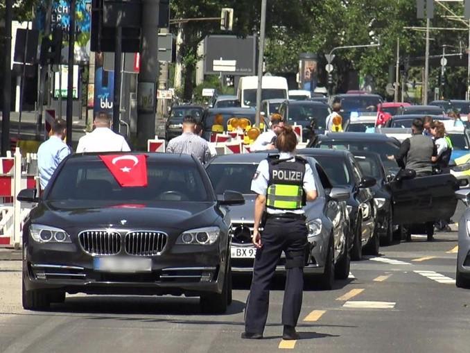 Eine Polizistin steht vor den Fahrzeugen eines türkischen Hochzeutskorsos. /dpa