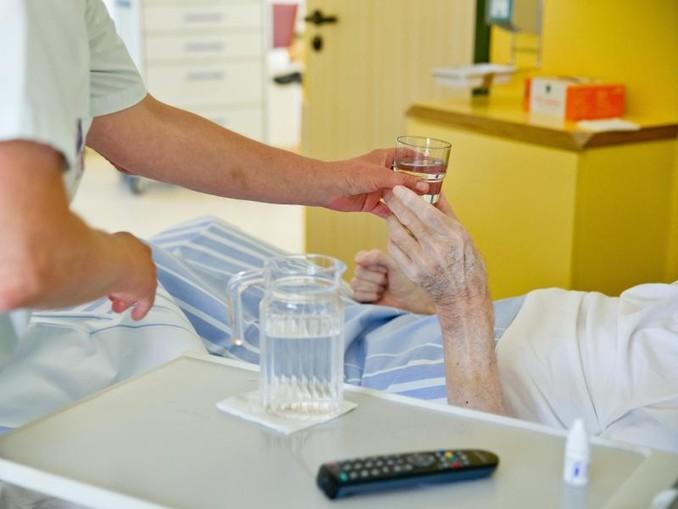 Eine Krankenpflegerin reicht einem Patienten in einem Klinikum ein Glas Wasser.