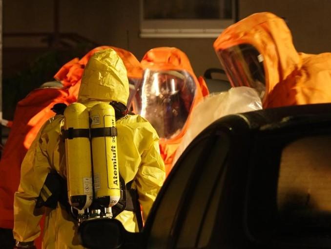 Feuerwehrleute sind in Schutzanzügen im Einsatz. /dpa