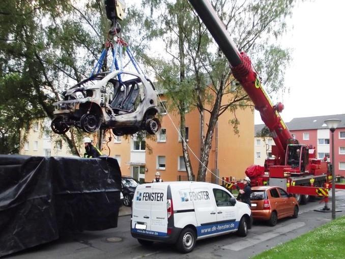 Ein Kranwagen der Dortmunder Feuerwehr hebt ein ausgebranntes E-Auto in einen Container. /Feuerwehr Dortmund/dpa