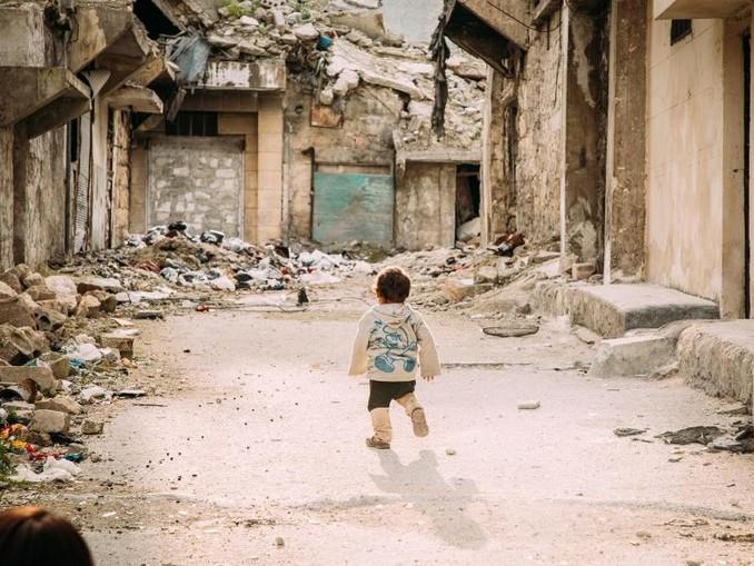 Ein kleiner Junge geht durch eine vom Bürgerkrieg zerstörte Straße in der syrischen Metropole Aleppo. /SOS-Kinderdörfer weltweit/dpa