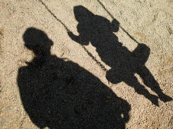 Der Schatten von einem Mann und einem schaukelnden Kind fallen auf Sand auf einem Spielplatz. /dpa