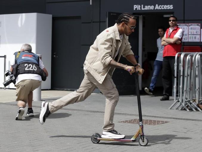 Läuft sich auf der Rennstrecke von Silverstone mit einem Roller warm: WM-Spitzenreiter Lewis Hamilton. Foto:Luca Bruno/AP