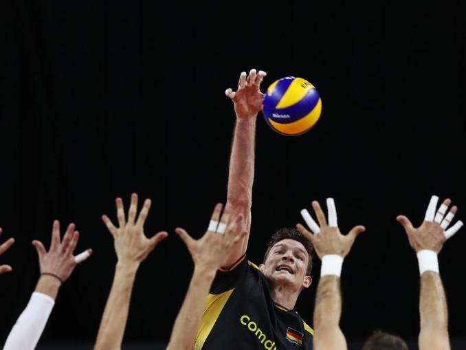 Der serbische Block wehrt einen Ball des Deutschen Christian Fromm (M) ab. Foto: Francisco SEco/AP