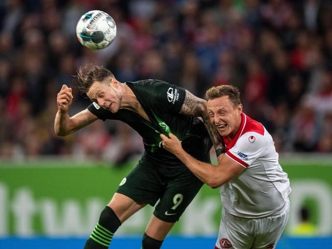 Düsseldorfs Robin Bormuth (r) und Wolfsburgs Wout Weghorst kämpfen um den Ball. Foto:Marius Becker