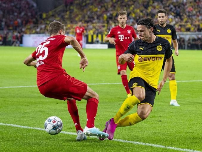 Treffen im Bundesliga-Topspiel aufeinander: Dortmunds Nico Schulz (r) und Bayerns Thomas Müller. /dpa
