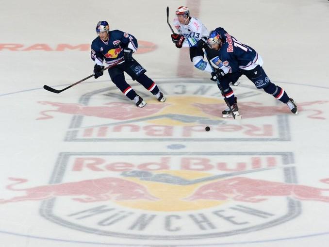 Spieler kämpfen um den Puck. Auf dem Boden ist das Logo des EHC Red Bull zu sehen. /dpa/Archivbild
