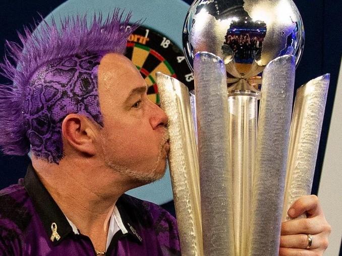 Der schottische Dartspieler Peter Wright herzt nach seinem Sieg die Sid-Waddell-Trophäe. /PA Wire/dpa