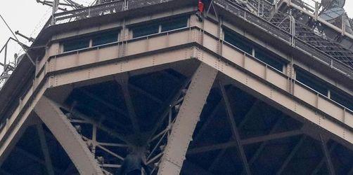 Mann klettert auf Eiffelturm und klammert sich fest
