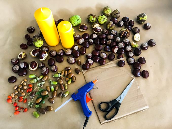 Basteln mit Kastanien, das braucht ihr: eine dicke Kerze (Größe nach Belieben), ein Stück Karton, Kastanien, Hagebutten, Nüsse, Eicheln, etwas Moos, Heißklebepistole, Schere. DIY