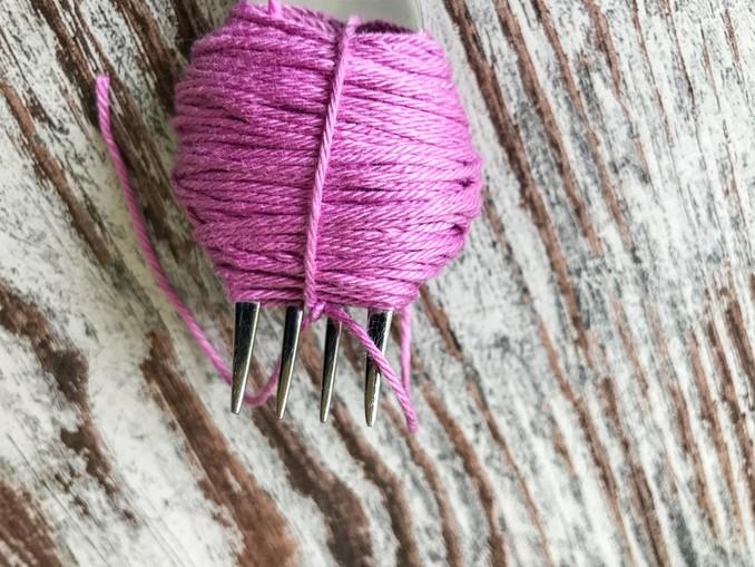 DIY: Pompoms. Doppelknoten um die gewickelte Wolle
