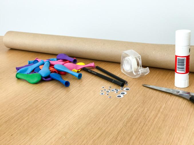 Alles was man für die selbstgemachten Geschenkverpackung braucht: Papier, Luftballons, Klebeaugen, Schere, Kleber, Edding