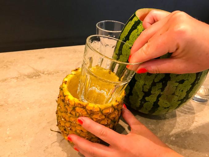 Glas in die ausgehöhlte Ananas geben