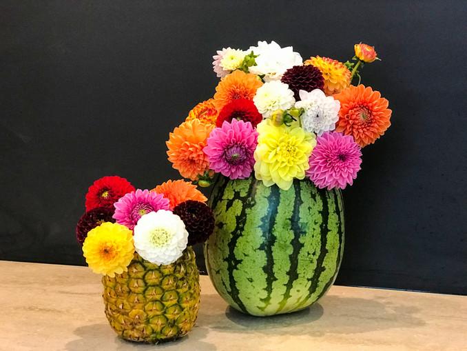 bunte Blumen in selbstgemachten Vasen aus Wassermelone und Ananas