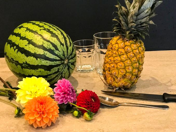 Wassermelone, Ananas. Messer, Löfel, frische Blumen, zwei Gläser